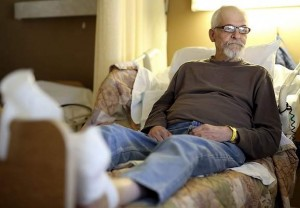 Rabb Sabin rests his injured foot while sitting in his bed at the Pacific Coast Manor in Capitola on Friday. Sabin is among hundreds in Santa Cruz County who live in their vehicles. (Kevin Johnson -- Santa Cruz Sentinel)